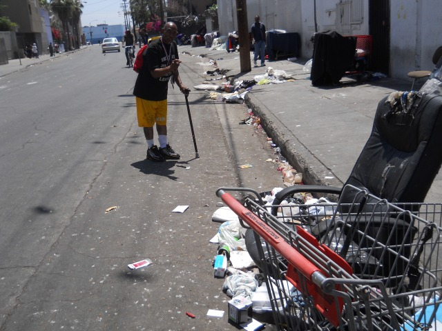 OG Man standing next to large piles of trash @ the southwest corner of San Julian & 6th- we NEED a trash can here